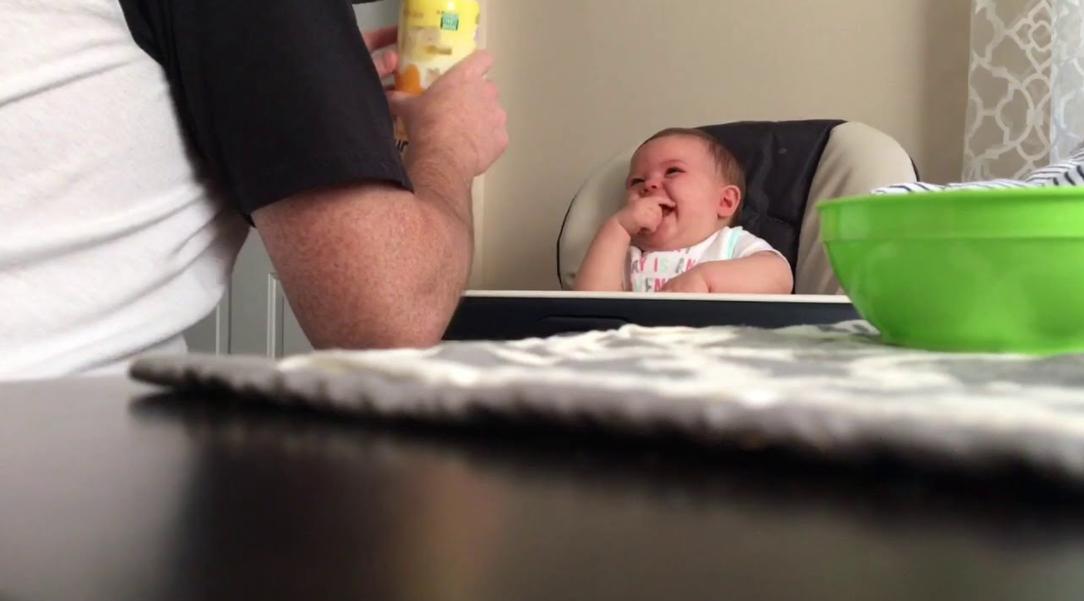 Tatăl lui se pregătea să îi dea de mâncare, dar bebeluşul avea chef de joacă. Priviţi ce amuzant este atunci când rade! Te cucereşte imediat.